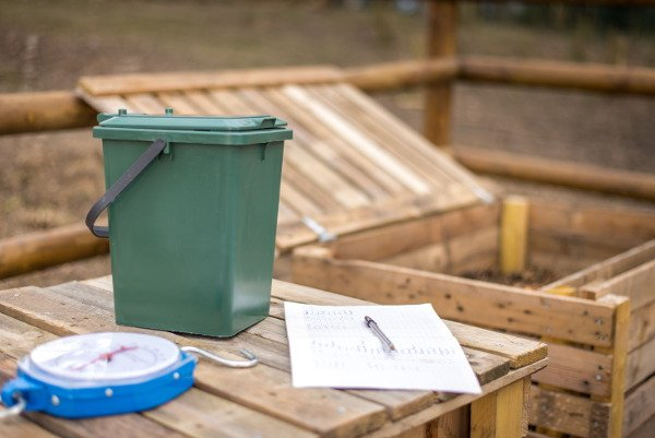 Compost bin with paper and thermometer.