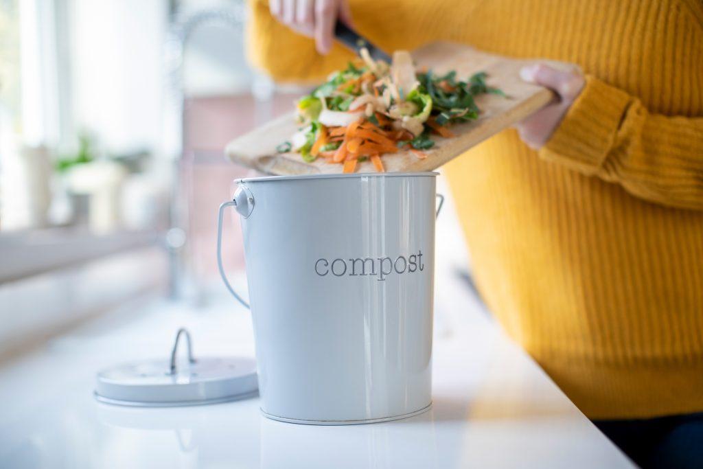 A woman scrapes veg scraps into a compost bin.