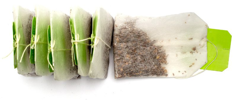 Row of teabags on a white background.