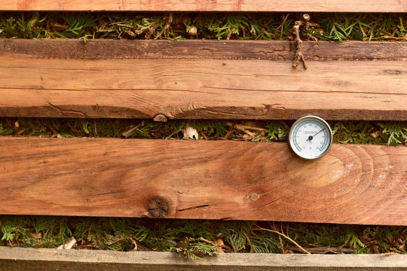 Thermometer in the side of a wood compost bin.