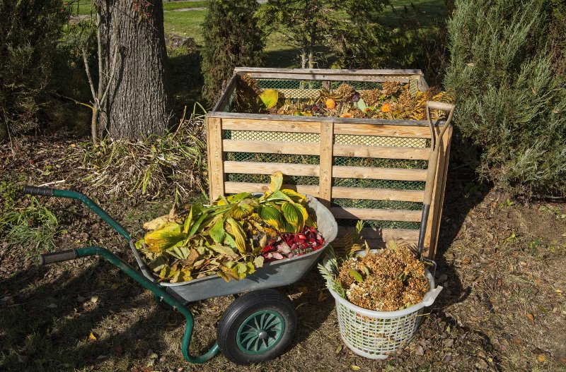 Compost bin with wheelbarrow and basket full of compost material.