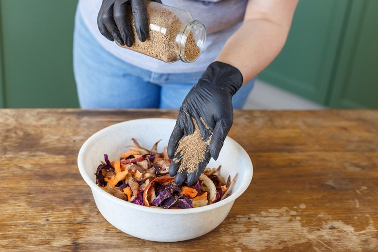 Adding Bokashi bran to compost material.