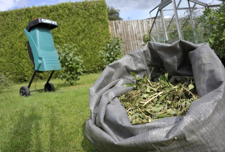 Compost shredder on lawn behind sack of clippings.