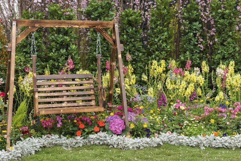 A swing in a flower garden.